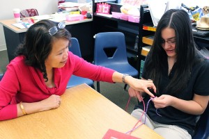 Heath Science teacher Mrs. Jocelyn Jaen carefully instructs sophomore Margaret Chang during a hand sutering lesson on Oct. 15.<br />Photo Credit: Hailey Basner