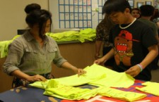 Jean Cruz and John Dulay fold staff t-shirts for Coyote U-Nite junior hospitality students.