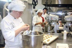Senior Mary Richen, juniors Katarina Bussman and Hristo Velikov quickly mix and bake cookies to fulfill Cashman Middle School's Open House order. <br />Photo Credit: Sahar Kanfi