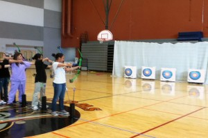 Junior Bryan Pluta and sophomores Charlene Hsu and Joy Hsu are practicing archery in the gym on Oct. 15.<br />Photo Credit: Raymond Tang