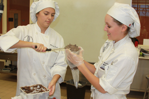 As part of the annual Cupcake wars, junior culinary students Mariana Ruffo and Katarina Bussman stuff their double chocolate icing tube before they shape and transfer it into the holders.<br />Photo Credit: Sahar Kanfi