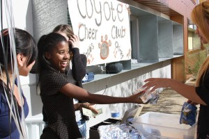 Sophomore and cheerleader Meya Holmes stands outside the fashion classroom selling Qdoba tacos during lunch. <br /> Photo Credit: Estefania Cervantes