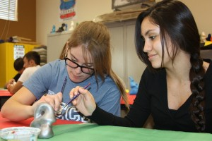 Freshman Danielle Frahm and sophomore Christen Gomez paint their sculpture together for Mr. Jared Ogden's sculpture project on Dec. 5.<br />Photo Credit: Kristian Hallegado