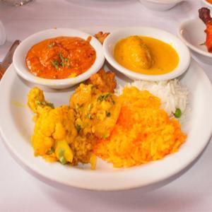 Creamy Chicken Tikka Masala and Shai Paneer fill the plate. Warm Aloo Kauli is placed upon vibrant basmati rice with sides of Tandoori Chicken and hot Chickpea soup.<br />Photo Credit: Tamara Navarro