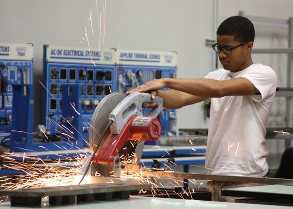 Head fabricator senior LaWone Hamilton cuts metal for his group's project creating a coyote statue. <br>Fabrication is one of the courses part of the Automotive Technologies magnet program.<br>Photo Credit: Allison Ho
