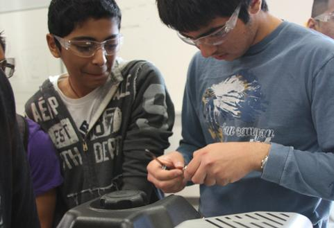 Roman Wahab and Kayvaan Adrangi, freshmen, try to figure out the correct placement of the spark plug.<br>Photo Credit: Emiliano Alvarez