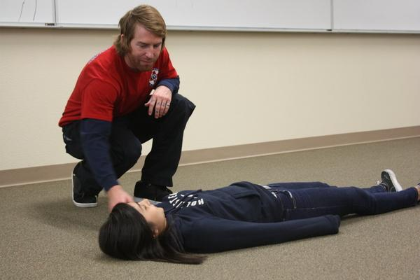 CPR trainers demonstrate using freshman Marisa Dichitang as a model, what to do in case a person passes out.<br>Photo Credit: Jenika Chiang
