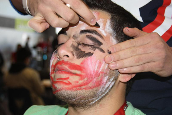 """Senior John Morales is painted by his partner, senior Zachary Pinion, in resemblance of the """"Joker"""" for the Battle of the Sexes competition on Monday, Feb. 25.<br>Photo Credit: Michelle Manuel"""