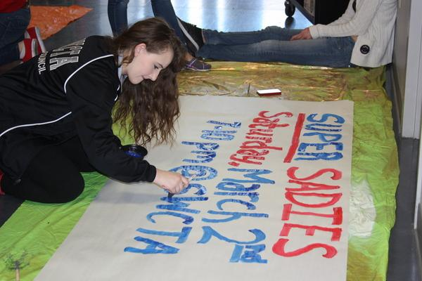 Freshman Rachel Martinez paints a banner to promote the Sadie Hawkin's dance on March 2.<br>Photo Credit: Kristine Faccinto