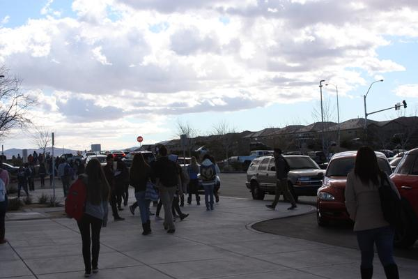 As students walk to the side of the road, more cars enter the parking lot, while others try to leave it simultaneously.<br>Photo Credit: Elaine Wong
