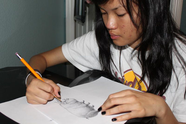 Shantil Gamiao, sophomore, draws a sketch of the Animal Farm character, Squealer, and the Russian propaganda team used during the Russian Revolution.<br>Photo Credit: Alex Nedelcu