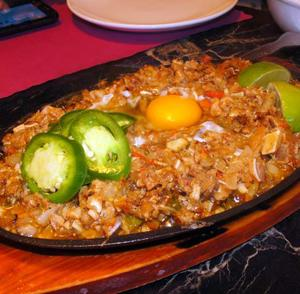 Sizzling Pork Sisig is a dish served hot with boiled, grilled, and chopped meat and organs. It is a savory hotspot of flavors.<br />Photo Credit: Tamara Navarro