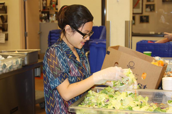 Freshman Hanna Tan scoops salad into a cup to package into a frozen meal dinner for the homeless on Mar. 20 <br>at Three Square.<br />Photo Credit: Southwest Shadow Staff