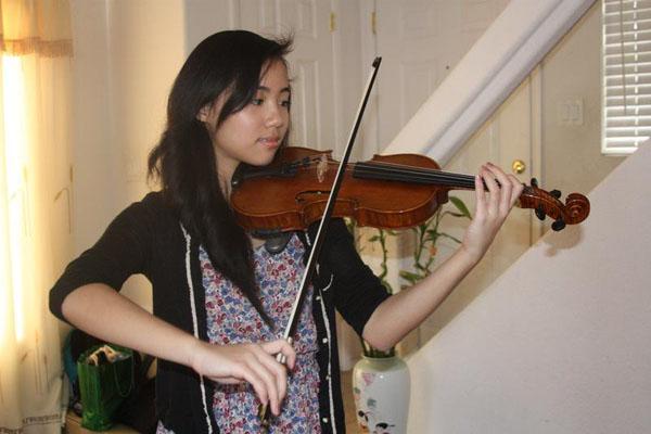 Freshman Xueying Zheng practices playing her favorite piece on the violin.<br>Photo Credit: Jenika Chiang