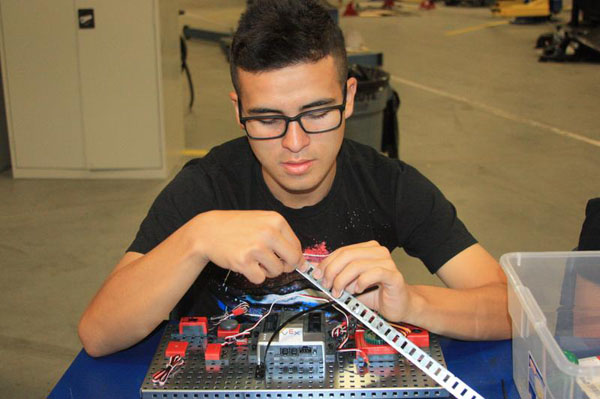 Sophomore Alejandro Alvarez Torres assembles his Vex Testbed by screwing in the specified parts, such as the encoder.<br>Photo Credit: Raymond Tang