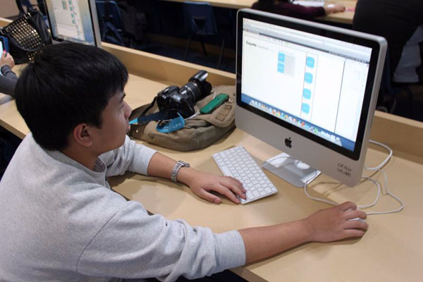 Journalism sophomore, June Santos, works on the yearbook spread he has to complete for his write-off competition before the upcoming trip to San Francisco.Photo Credit: Hailey Basner
