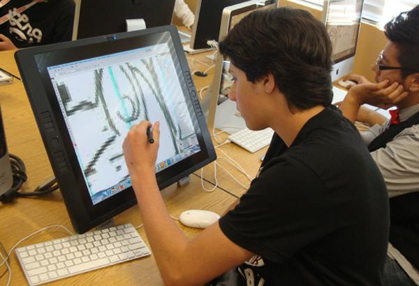 Freshman Adam Rifat sketches out a design for the t-shirt he is making for a first grader.<br />Photo Credit: Mrs. Maureen Clark