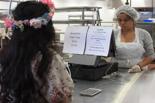 Senior Christian Molina gives her order to the cafeteria staff member.<br>Photo Credit: Bree Eure