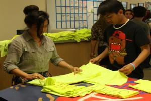 Jean Cruz and John Dulay fold staff t-shirts for Coyote U-Nite junior hospitality students. Photo Credit: Raymond Tang