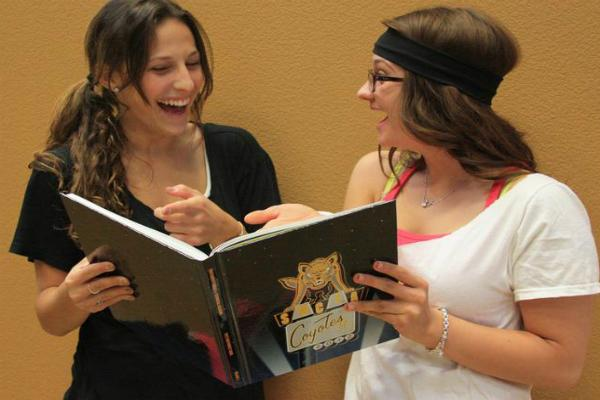 High school friends, Marina and Jordan, share a laugh at their high school reunion when looking at an old yearbook from their junior year.