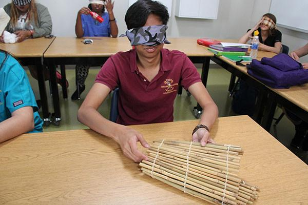 """Senior Alan Klumprasent toys around with a bamboo mat using his """"touch"""" sensory skill whilst blindfolded in attempt to identify it.  Photo Credit: Jenika Chiang"""