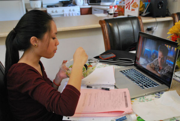 "Sophomore Miruel Talaro ignores her math homework as she watches a movie and eats her salad. There were plenty of math packets to finish, but she chose to watch and eat, instead. ""When I don't like the homework, I do menial tasks like eating or watching Netflix to put off doing work,"" Talaro said.  Photo Credit: Patricia Ascano"