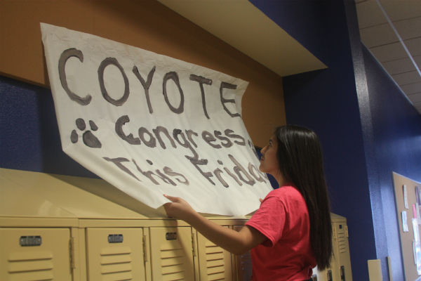 Student Council will be hosting the third Coyote Congress this year on Friday, Nov.1, and the topic this month is class t-shirts. Sophomore PA Senator Citlali Tinoco hangs up a poster promoting the event.  Photo Credit: Emily Yu