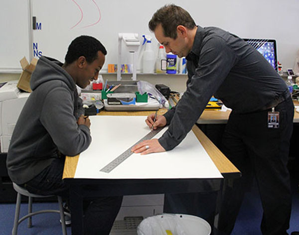 """Mr. Jared Ogden teaches senior Mehaki Asare how to draw perspective on a one-on-one level. """"I guess it's easy to draw perspectively, but it's actually kind of confusing to,"""" Asare said.  Photo Credit: Jenika Chiang"""