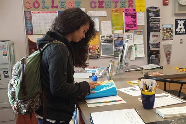 Junior Andrea Galvan checks the presentation sign up sheet in the College Center. All students must sign up for the presentations in order to be eligible to attend. Photo Credit: Althea Gevero
