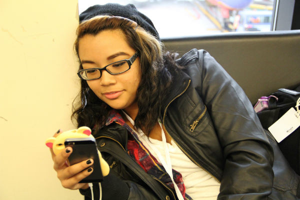 Sophomore Brittnie Truax uses her phone out of boredom while waiting at the Logan International Airport for a new flight back to Las Vegas.  Photo Credit: Tamara Navarro