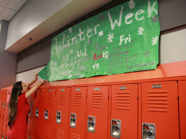 """Senior Alexis Lane adjusts the """"Winter Week"""" banner for students to see easily while walking down the hallways. """"Student Council spent a lot of time making the banner, so hopefully people will read them and know what to dress up for,"""" Lane said.  Photo Credit: Jen Chiang"""