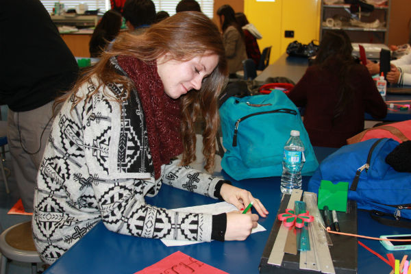 """Junior Elizabeth Tchernogorova works on her comic strips during art. The art classes created comic strips for the Boulder Boat company to put in the yearbook as an ad. """"It was cool actually using our art skills for stuff outside of the classroom,"""" Tchernogorova said.  Photo Credit: Helen Abraha"""