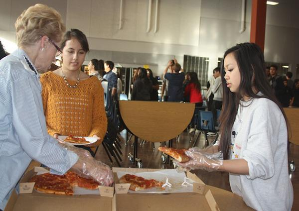 Mrs. Vicky Smith and junior Maggie Yuen serve a slice of pizza to junior Alexa Munoz during HOSA's annual holiday party. Club members paid $3 prior to the party so that the pizza could be purchased.Photo Credit: Mayra Valdez