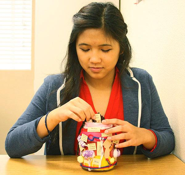 """Sophomore Kelly Bui works on a jar craft. It was a model of the skin's layers. """"Crafting projects are always rewarding and enjoyable to do. Hopefully everyone can experience receiving or making a craft,"""" Bui said.Photo Credit: Calida Tam"""