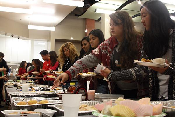 """Foreign language students serve themselves food for the Culture Fest. Students had the option of being in a group of three or two and prepared a dish that was of French, Spanish, or German origin. """"I had two full plates of food and I enjoyed trying food from different cultures,"""" said sophomore Acel Soriano.Photo Credit: Jorge Carrera"""