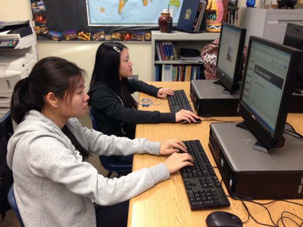"""Sophomores Samantha-Juliane Lam and Maggie Gee research their destination to compose a trip itinerary for a three day vacation. They plan to travel to Reno, NV. """"I really like my itinerary. I kind of want to go to Reno and follow it now,"""" Lam said.  Photo Credit: Jen Chiang"""