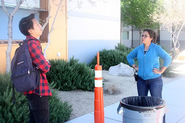 Sophomore Brandon Villanueva is stopped by Campus Security Monitor Ms. Mary Flores as he tries to cross the orange cones during lunch time. All students must remain within the confided area marked by the orange cones to ensure student safety and prevent further littering.  Photo Credit: Jen Chiang