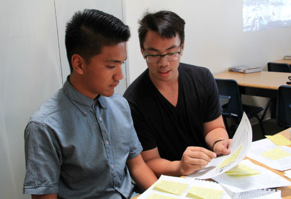 """Sophomores Karel Saquing and Christian Reyes review what they are going to say in the debate. They represented option four, to avoid foreign entanglements. """"I enjoy debating and world history, so I really enjoyed participating in this simulation,"""" Saquing said.  Photo Credit: Jen Chiang"""