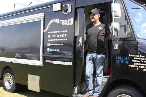"""Delicioso Food Truck Owner Jorge Cortez stands by his food truck door before opening up shop for lunch hour. He was looking around and relaxing before a wave of customers come. """"There's only two of us. A cashier and a cook,"""" Cortez said.  Photo Credit: Jen Chiang"""