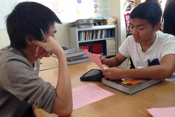 """Sophomores Skyler Lao and Kristoffer Medina review the 43 topics related to World War II before making the final decision. They have both chosen to create an Aurasma on their topics. """"I think this assignment is an interesting way to take on the topic of World War II,"""" Medina said.  Photo Credit: Jen Chiang"""