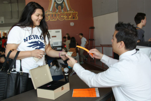 """Senior Keilah Gonatice purchases a $2 wristband from Dean Mr. A. Yee so that she could wear a hat and sandals on Fri., May 9. Wristbands will be sold during both lunches, and all proceeds will go towards Dr. Lilly Sifuentas' treatment recovery. """"It's really nice to be able to give back,"""" Gonatice said.  Photo Credit: Jen Chiang"""