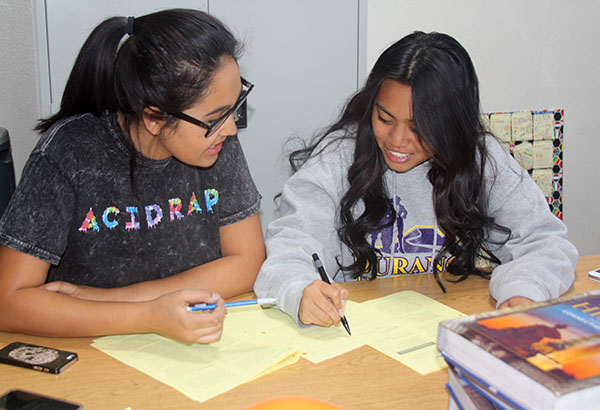 """In preparation for the debate, sophomores Isabella Delarosa and Desiree Galera discuss their option to make a script for their presentation. Students had five to eight minutes to pitch their option and answer any questions. """"It was a good way to learn, but it was very stressful because there were large groups,"""" Galera said.Photo Credit: Acel Soriano"""
