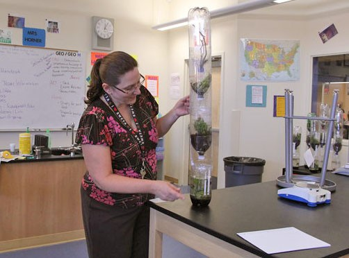 "Advanced Placement Environmental Science teacher Mrs. Martha Horner explains the components of the eco column to the class. Students created their own ecosystems to help them understand the interactions between all of the ecosystems while also preparing them for their AP exam in May. ""This experiment is about teaching the students the different things in our ecosystem,"" Horner said.  Photo Credit: Helen Abraha"