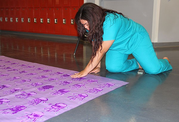 "Senior Karen Santos, Banner and Posters Committee Chair, adds finishing touches to the backdrop for Week of Respect. The backdrop will be in the cafeteria during the event. ""The purpose of the banner is called a ""step and repeat"" in which students will take photos with the poster as their back drop. As this is done, the students will post the photo on any social media website using the hashtag ""#SouthwestRespect"" and will then have the opportunity to sign their name on one of the handprints,"" Santos said.  Photo Credit: Alex Nedelcu"