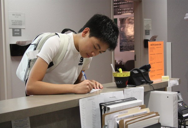 """Upon arrival, tardy students must report to the main office in the A building to fill out a tardy slip. Students who have served detention must also check out at the same location. """"I've been tardy before and I find this new policy great because it's more lenient towards students,"""" junior Jaime Sesgundo said.  Photo Credit: Acel Soriano"""