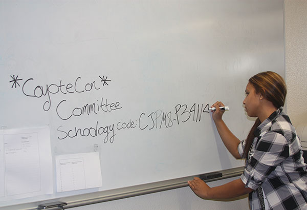 """Senior Gabriella Brubaker writes down the Schoology code for students to join the Coyote-Con group. Coyote-Con will take place on Nov. 22 and an informational meeting will be held on Oct. 15 from 2 p.m. to 4 p.m. in room B113. """"The schoology group is there to remind the students about what's going to be at the event and give them something to look for. I think everyone who's interested in going to it should join the group and stay updated,"""" Brubaker said.  Photo Credit: Acel Soriano"""