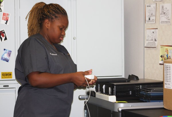 "Junior Aundriana Gaston picks up her iPad at E136 and ensures her iPad and charger are working. Students who obtain a school-issued iPad are provided with a case, screen protector and charger. ""I was so glad to receive my iPad because all my classes are dependent on technology,"" Gaston said. Photo Credit: Acel Soriano"