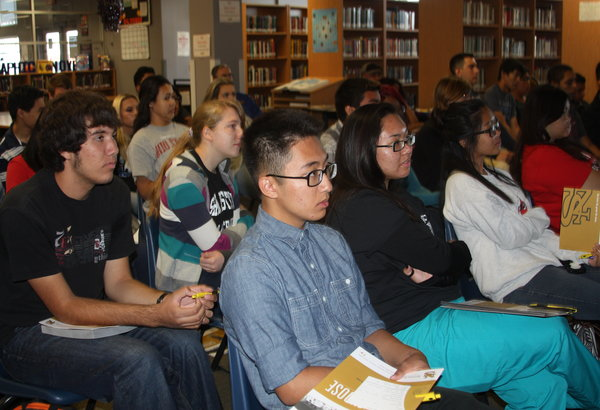 """Seniors listen attentively as a presentation is given. In the library, Nevada State College gave a seminar on their school. """"The scholarship presentation really opened my eyes. I've been applying for scholarships, but I've never heard of the ones that were described in the presentation,"""" senior Zak Wong said.  Photo Credit: Helen Abraha"""