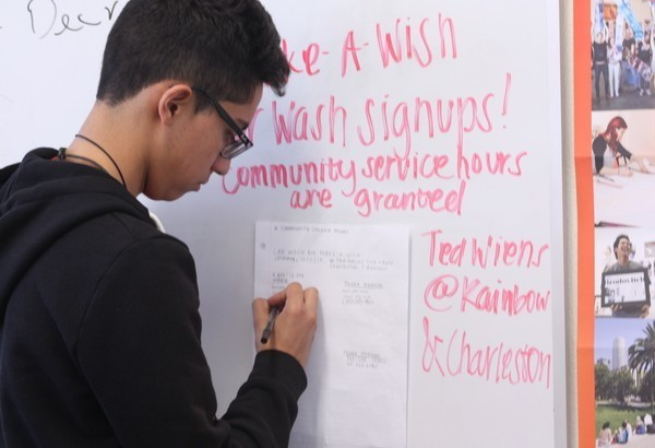 """In Mr. Perry Annett's room (B210), junior Tonatiuh Gomez-Aramburo signs up for the DECA car wash that will take place on Oct. 11. As well as being a community service project for the State Career Development Conference (SCDC), all proceeds will assist in reaching a $5000 goal for the Make A Wish Foundation. """"The results not only will benefit DECA, but will help a child in need. That is one of the few opportunities to make someone truly happy and definitely worth my time,"""" Gomez-Aramburo said. Photo credit: Brittnie Truax"""