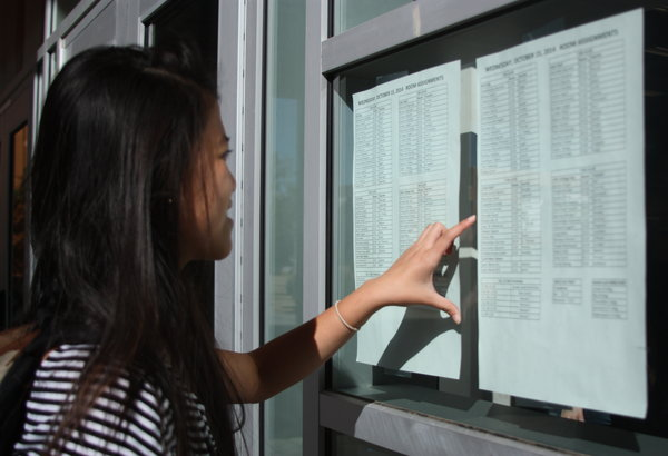 """Junior Serena Torres checks her room assignment for the PSATs. Scholarships are offered to the highest scoring juniors in the nation. """"I'm really nervous for the PSATs and the SATs because it's important for college and will ultimately decide my future,"""" Torres said.  Photo Credit: Acel Soriano"""